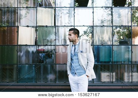 Portrait of stylish handsome young man with bristle standing outdoors and leaning on wall.