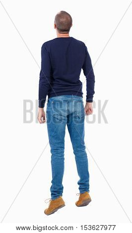 Back view curious guy who stood on tiptoes, and peering up. tanding young guy. Rear view people collection. backside view of person. Isolated over white background. Man in warm jacket stood on tiptoe