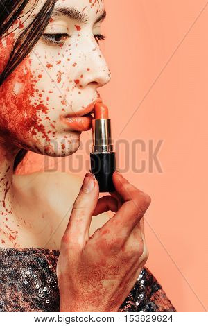 Halloween zombie girl or pretty young woman with brunette hair with wounds and blood puts red lipstick on lips on pink background