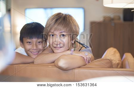 Mother & Son Smiling At Camera On Couch
