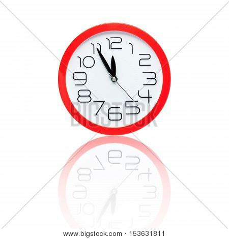 red alarm clock showing five minutes to midnight with reflection