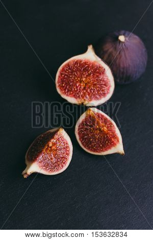 figs on a dark wood background. tinting. selective focus on the front figs slice in the bowl