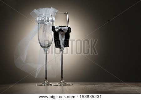 Elegant champagne glasses dressed in mini suitsof bride and groom