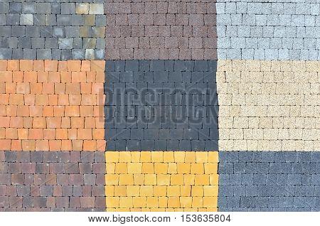 Urban background. Samples of trapezoidal pavement tiles of black orange yellow white gray.