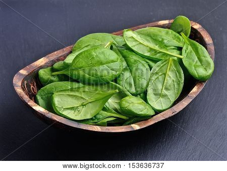 Fresh spinach on a graphite background .