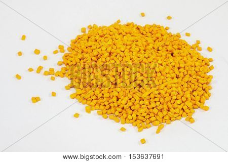 yellow plastic polymer granules on white background