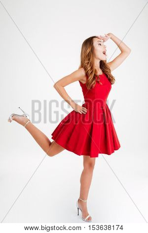 Happy playful young woman in red dress standing and looking far away over white background
