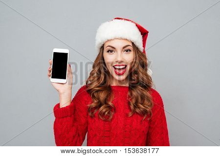 Smiling young woman in santa claus hat showing blank screen smartphone over gray background