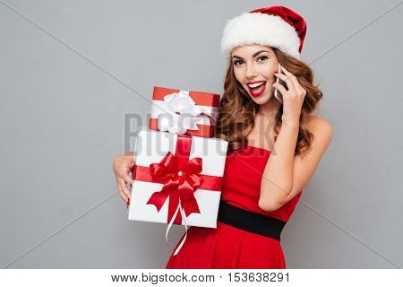 Smiling girl with Christmas gifts calling on phone. Santa's helper. Girl on dress and Santa's hat