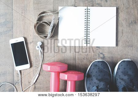 Flat lay of empty notebook cellphone and sport equipment on wooden background. Sport wear Sport fashion Sport accessories Sport equipment copy space top view with vintage filter