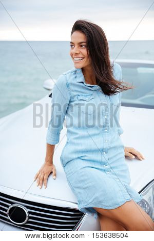 Smiling beautful woman standing by her expensive car