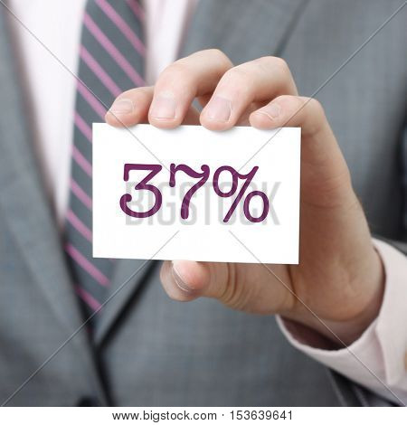 37% written on a card held by a businessman