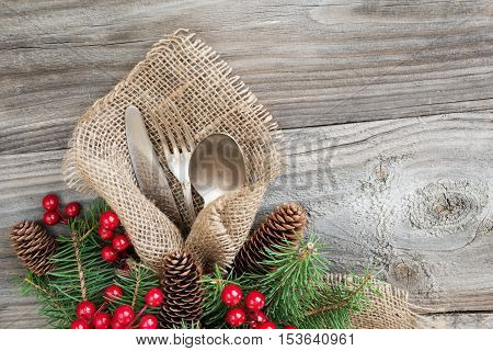 Christmas table with Christmas decoration: old knife spoon and fork lie on the sacking napkin as well as red holly berries and green spruce branch which is located on an old wooden table with space for text