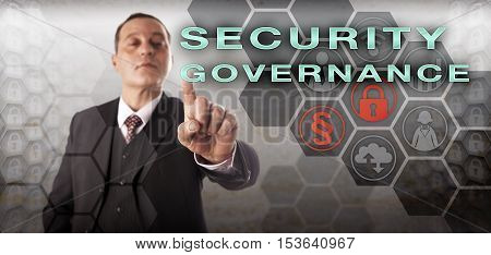 Confident male business manager is touching SECURITY GOVERNANCE onscreen. Information technology metaphor and business concept for the enforcement of an enterprise computer security policy.