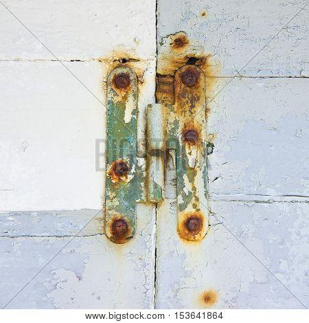 Old hinge of a white wooden door