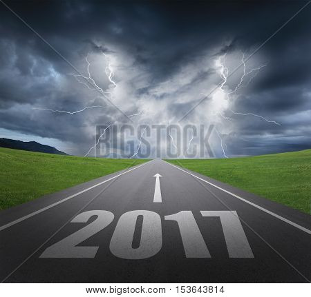danger to 2017 new year concept rainstorm clouds and lightning with asphalt road
