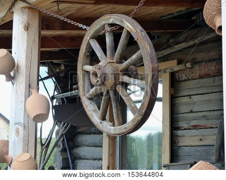 Obsolete old wheel of the horse cart. Hanging under the roof of a rural hut. Retro. Closeup. Ural, Russia.