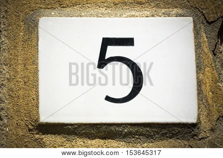 Door number five sign on weathered wall