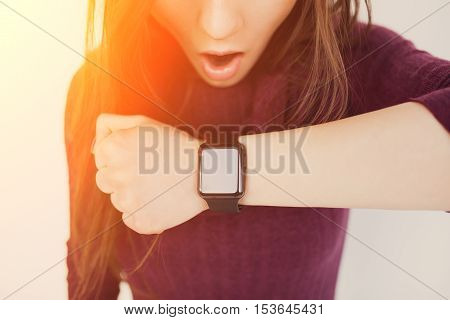 Young Woman looking at Touchscreen Smart Watch at Home. Girl being late concept.