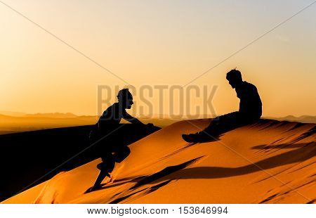 Young Man Encourages His Friend On A Dune Sahara