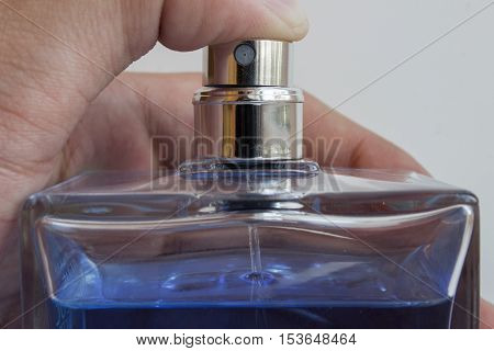 Men's fragrance in his hand close-up. Finger presses the diffuser.
