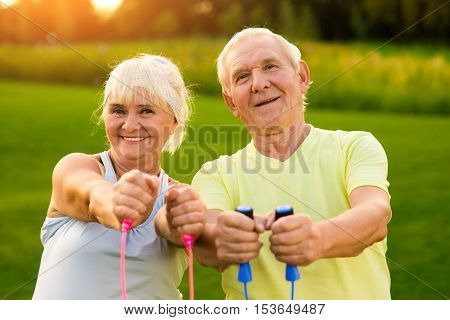 Smiling couple of seniors outdoor. People holding skipping ropes. Small victories in sport. Improve your results.