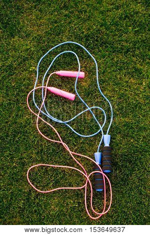 Jump ropes on grass. Pink and blue skipping ropes. How to train cardiovascular system. Agility and endurance.