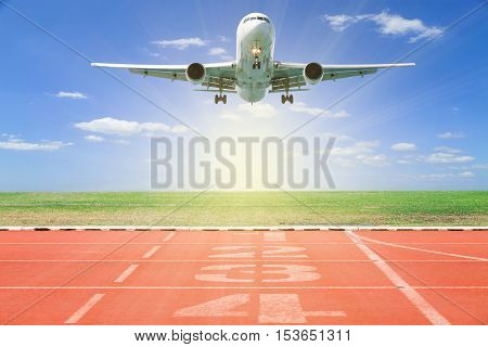 Airplane take off with Start and Finish point of race track Running track number in front of tracks in stadium with beautiful green grass and blue sky scenery background open high season travel and tour concept