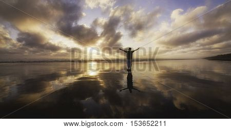 Man with over stretched arms looking towards sunset.