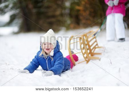 Two adorable little sisters enjoying sleight ride on snowy winter day