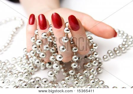 Woman hand and silver beads.