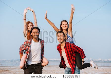 Two cheerful young men standing and holding girlfriends on their backs outdoors