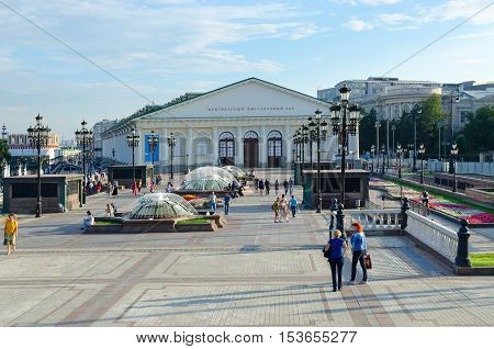 MOSCOW RUSSIA - JULY 23 2016: Unidentified people walk on Manezhnaya Square near Central Exhibition Hall