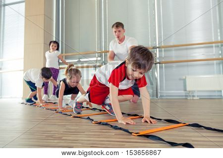Happy sporty children in gym. pressing, working with a coach. children's fitness