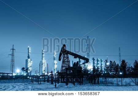 Oil pump and wellhead at the background of refinery by night. Oilfield during winter. Oil and gas industry. Toned.
