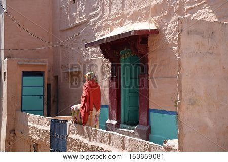 JODHPUR, RAJASTHAN, INDIA - FEBRUARY 09, 2016 - Unidentified indian woman in traditional dress sitting outside her colorful house