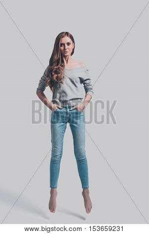 Beauty in mid-air. Mid-air shot of attractive young woman in casual wear holding hands in pockets and looking at camera