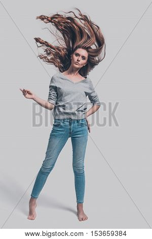 Beauty in motion. Full length studio shot of attractive young woman with tousled hair posing against grey background