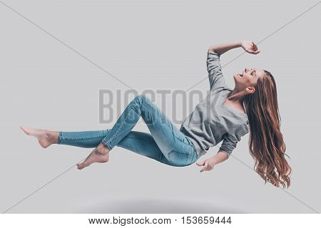 Hovering in air. Full length studio shot of attractive young woman hovering in air and smiling