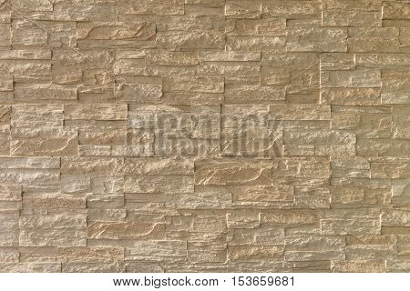 light brown stone brick exterior wall in hard light emphasizing stone's textures and depth