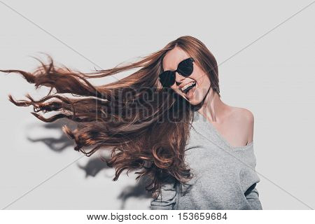 Hair like fire. Attractive young smiling woman with tousled hair looking away while standing against grey background
