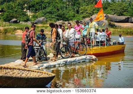Hampi, India - November 20, 2012: Unidentified tourists crossing the Tungabhadra River with traditional small ferry Hampi Karnataka India