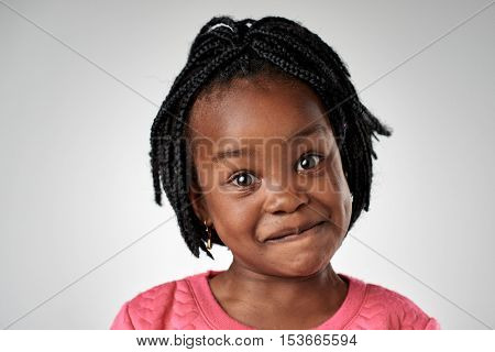 Young african black child making funny  silly face