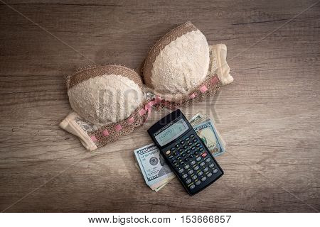 beige bra and calculator with us money