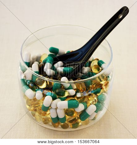 A scattering of different  tablets in a transparent bowl. Pills  on a woven background. The warning about the possibility of addiction to the medication and you exceed the dosage. Horizontal.