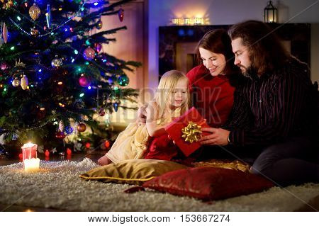 Young happy family of three unwrapping Christmas gifts by a fireplace in a cozy dark living room on Christmas eve