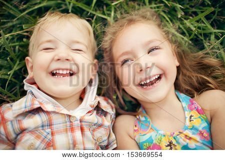 Above view portrait of two happy smiling kids lying on green grass. Cheerful brother and sister laughing together.