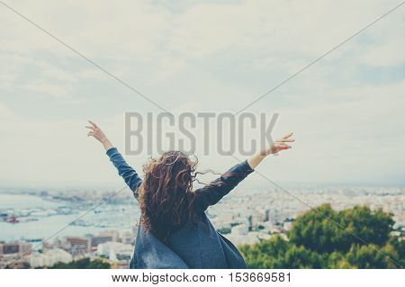 Back view of cheerful curly young woman with hands up. Freedom concept.