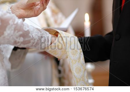 Bride And Groom's Hands And Priest's Cassock