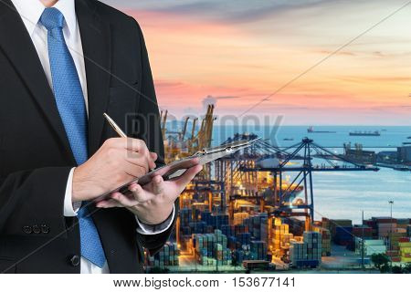 Businessman writing notebook for trading and logistics with blurred cargo container terminal at port in background. Business trading and logistics concept.
